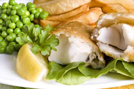 Fried fish and chips with lemon and peas
