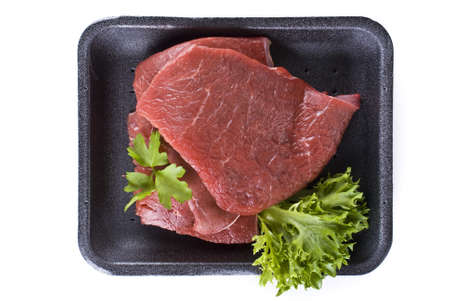 Raw beef frying steak in black tray  isolated over white background Stock Photo - 9741496