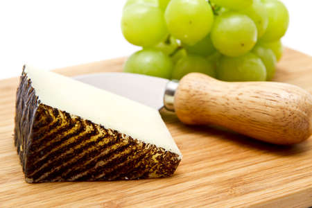 Manchego cheese and green grapes on chopping board photo