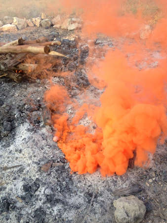 Orange smoke bomb next to a fire