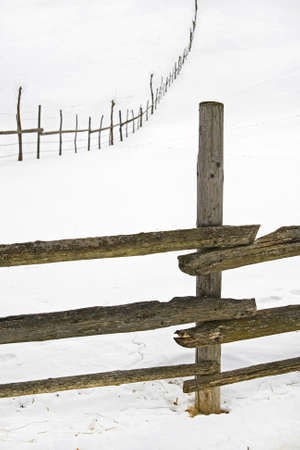 fence post: wooden fence for animals on a hill in winter Stock Photo
