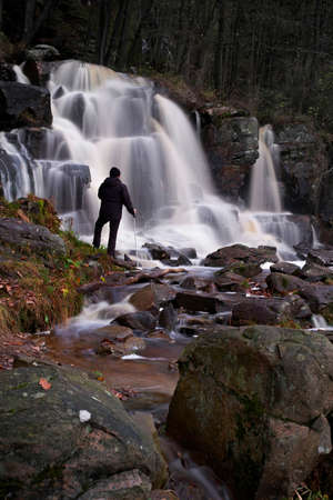A man is watching a waterfall.