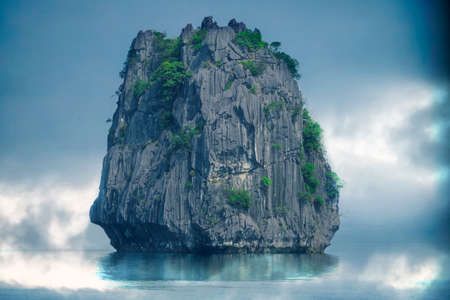 Large cliff in fog surrounded by water