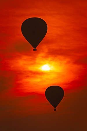 2 air balloons against red sky.