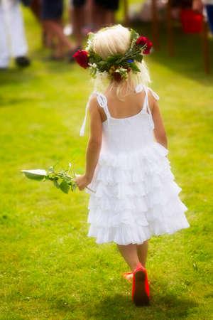 Vigilia di mezza estate con una bambina vestita di bianco con una ghirlanda tra i capelli.