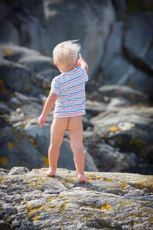 Little guy shows his butt and stands barefoot on a hot rock. Stock Photo