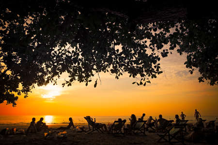 People sitting on the beach in Thailand and enjoying the sunset.
