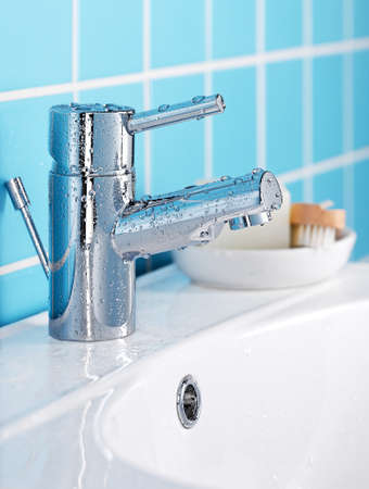 Faucet on a washbasin against a blue tiled wall.