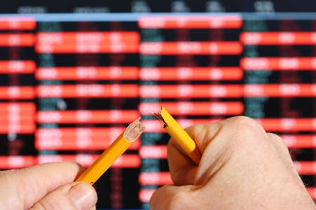 share prices: Stockmarket sreen with falling share prices,snapping pencil with stress