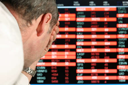Stockmarket sreen with falling share prices, depressed trader with head in hands