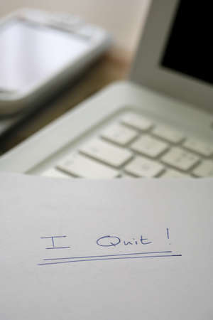 resignation: I quit, resignation note on a desk in an office environment.