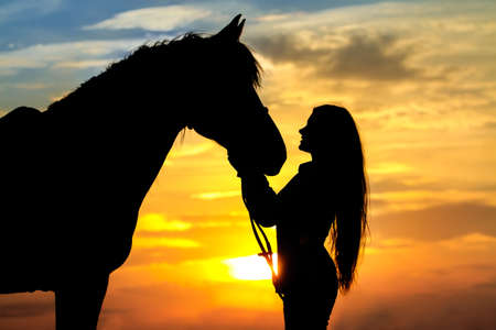 Girl with horse silhouette against sunset sky