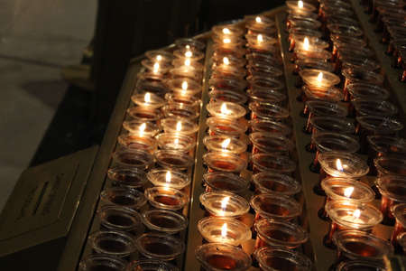 Group of candles lined up in display glowing