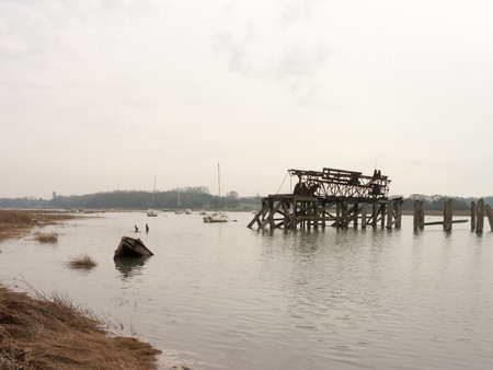The river colne with a submerged boat and old structure. Stock Photo
