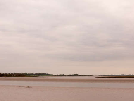 Low tide summer sky nightfall grey clouds mood and reds with river running through in wivenhoe essex uk england