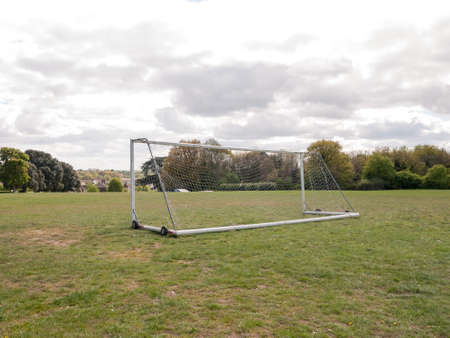 An Empty and Unused Goal Post with A White Net in the Middle of A Park with Grass and Soil on the Ground, Wheels on the Frame to Help Move it and Houses and Trees in the Background, Used For Football and for A Goal Keeper No Person Seen From Behind in Spr