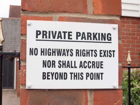 a sign outside near a private residential old people car park saying private parking no highways rights exist no shall accrue beyond this point white and black on brick warning restriction english uk road law 版權商用圖片