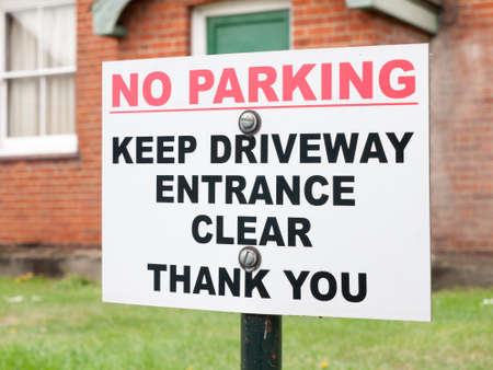 disallow: a sign outside a house saying no parking keep driveway entrance clear thank you red and white and black on post nailed screwed warning restrictions law