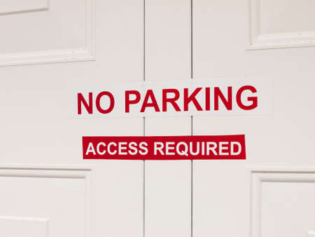 inform information: a white and red no paring access required sticker sign attached to outside garage door restriction english uk law private house car space driving