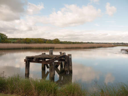 a landscape shot of a beautiful serene lake with a wooden structure rotting platform