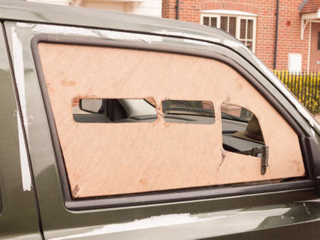 a car window boarded up with wood panel outside broken