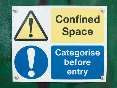 confined: A photograph of typical signs warning of danger on a building site box