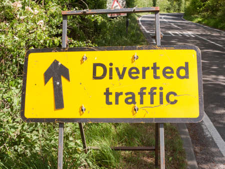 a yellow road traffic construction sign for design graphics saying diverted traffic on the side of a road and with a black upwards arrow metal sign outside motorway countryside law