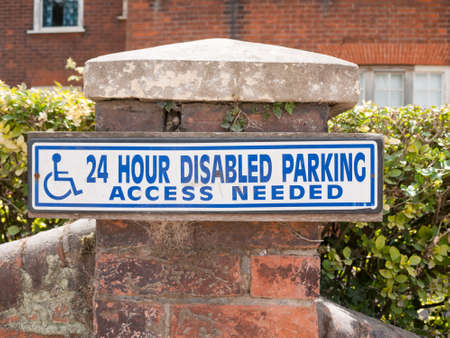physical impairment: blue and white 24 hour disabled parking access sign on brick post outside