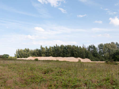 sand quarry: piles of sand from quarry in distance of field with sky above; Essex; UK Stock Photo
