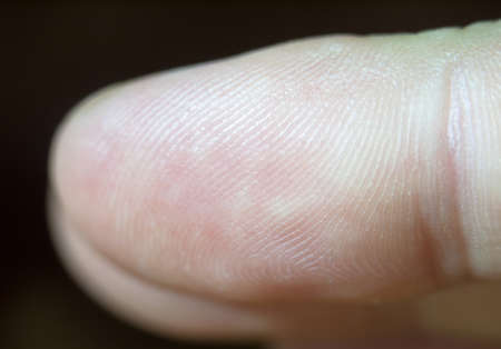 close up macro detail of a finger tip and its print; UK