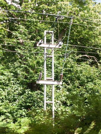 electrical metal pylon on train tracks in summer light; England; UK