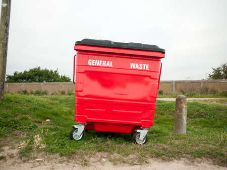 a red general waste bin single one outside on grass; England; UK Stock Photo