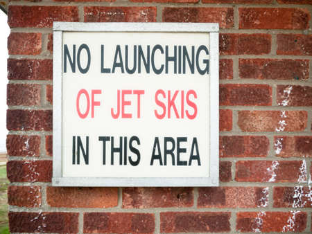 old retro sign lettering on wall saying no launching of jet skies in this area; England; UK