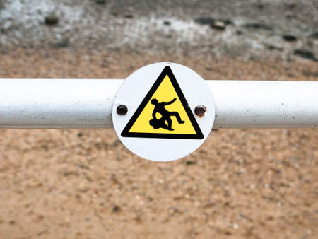 a funny sign on pole indicated a man slipping, slippery surface sea front; England; UK