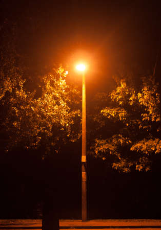 A bright glowing street lamp light in the dark outside at night; Essex; England; UK