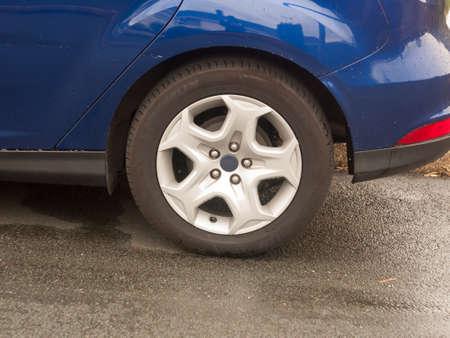 curve road: close up of back wheel rim cap blue car; England; UK
