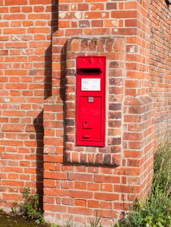 delivery service: close up of red royal mail box in brick wall postage; England; UK Stock Photo