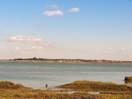 beautiful scene of river with boats grassland in front blue sky and clouds village skyline in background; essex; england; UK