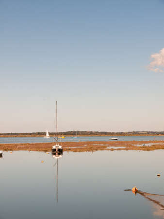 boat moored in estuary scene with mast reflected in water blue sky; essex; england; UK
