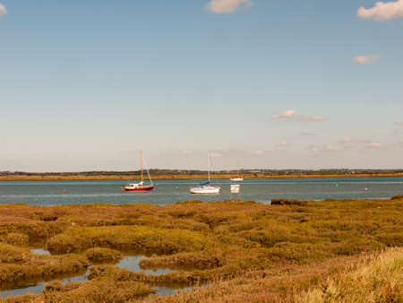 beautiful scene of river with boats grassland in front blue sky and clouds; essex; england; UK