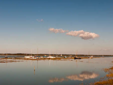 beautiful estuary scene with blue sky moored boats, masts, and reflection of cloud in water surface; essex; england; UK
