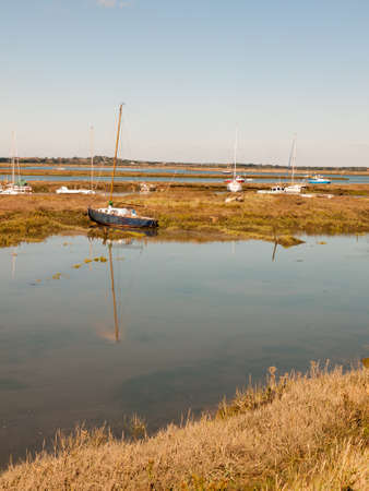 row boats parked in stream river estuary in tollesbury maldon essex; essex; england; UK Stock Photo