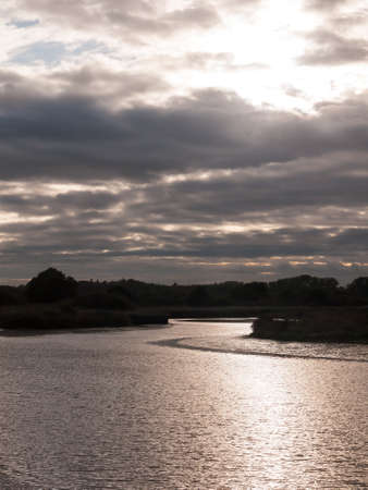 sun setting through dramatic clouds and onto lake river stream water; Essex; England; UK Stock Photo