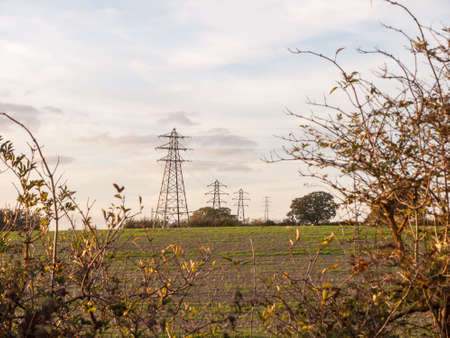 Electricity pylons row of far distance field farm agriculture. Essex. England, UK
