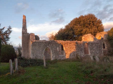 soft sunset light on old ruined burnt down Alresford Church outside graveyard; essex; england; uk