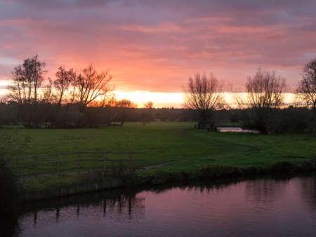 red sun setting sky dramatic autumn over empty open green countryside night dark lake; essex; england; uk Stock Photo