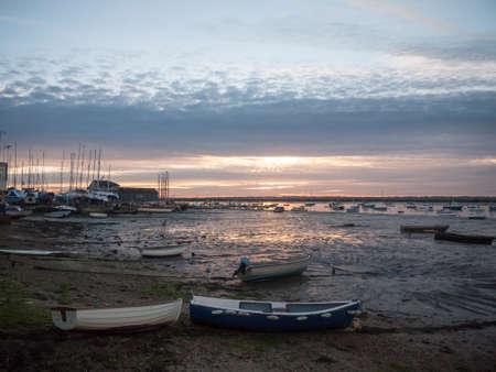 sun set sky dramatic clouds sea front beach harbor marina boats moored landscape; west mersea, essex, england, uk Stock Photo