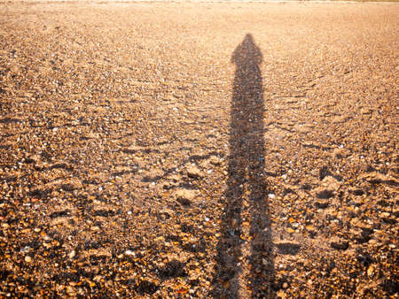 cool silhouette reflection shadow shade in sand beach cobble texture floor; west mersea, essex, england, uk