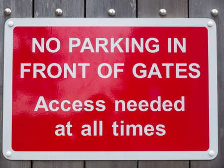 no parking in front of gates access needed at all times red parking sign.