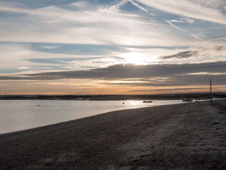landscape horizon beach sun set sky dramatic beautiful; west mersea, essex, england, uk Stock Photo
